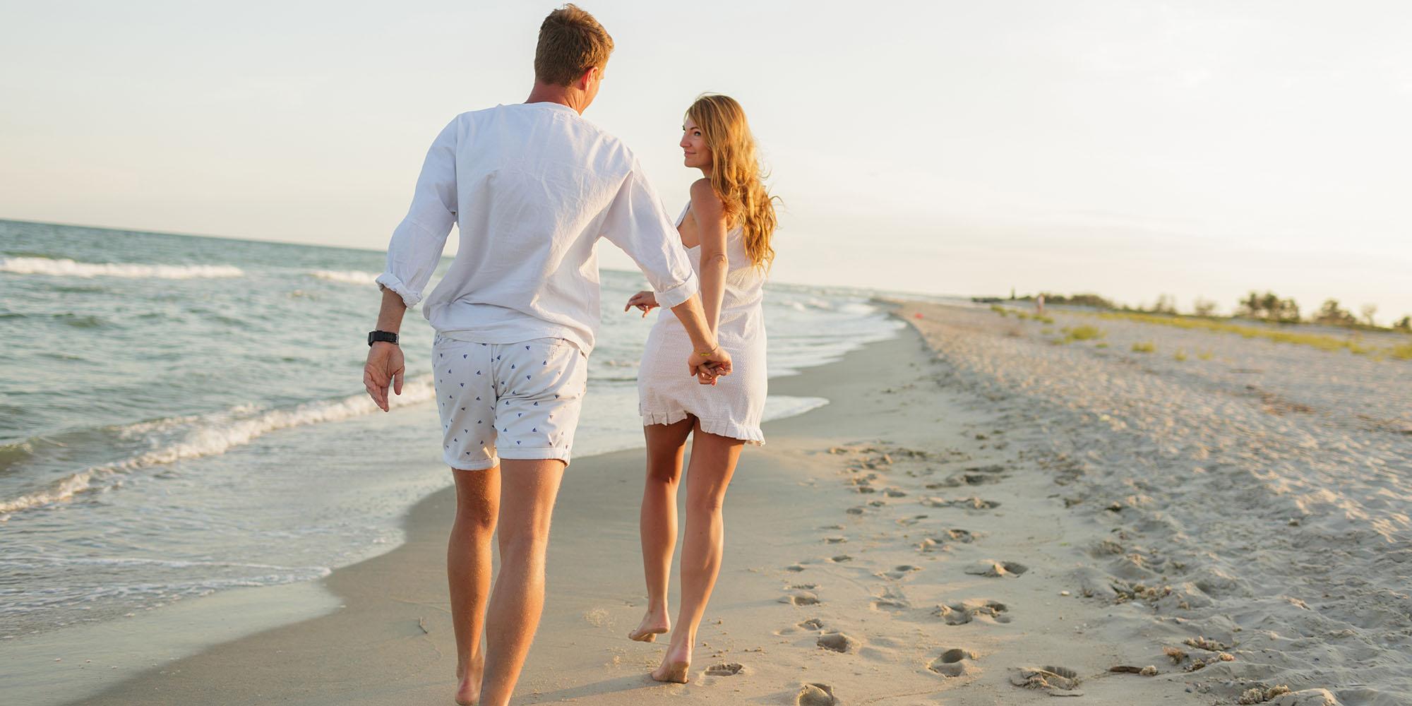 Young Beautiful Couple Walks Along The Seashore